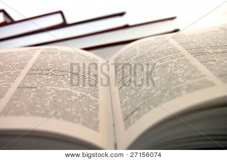 An open book against white background. , most of the text is thrown out of focus and is not readable.