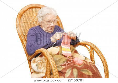 grandmother knits in an armchair-rocking chair