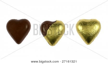 Three wrapped and unwrapped chocolate hearts isolated on white