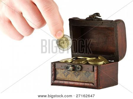 Old casket full of coins and a hand holding two euros coin