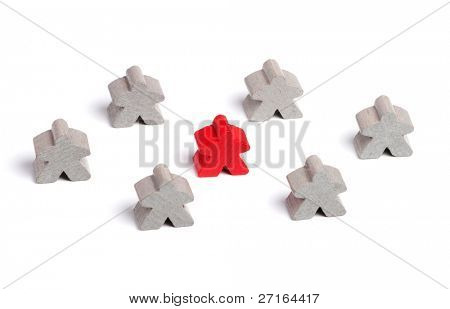 Red wooden figure surrounded by gray ones on white background