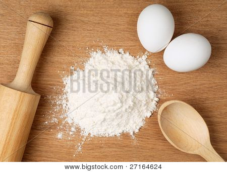 Flour and eggs on a wooden board