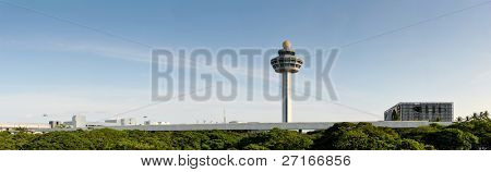 The control tower of Changi Airport in Singapore. this panoramic shows off the garden city's green trees, blue skies and cleanliness. the air traffic control tower sticks out into the sky.