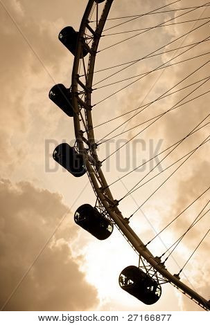 The Singapore Flyer rotates slowly under the clouded sky above. Sunset causes the flyer to silhouette against the sky