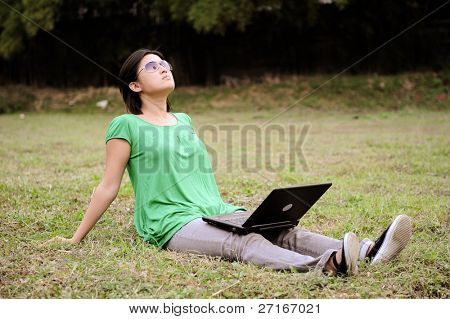Asian girl does her business in the park as she soaks up some sun.