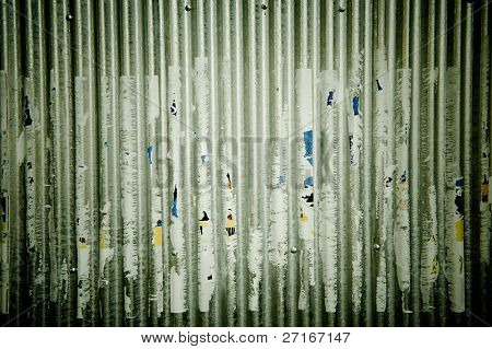 Corrugated metal with a torn poster