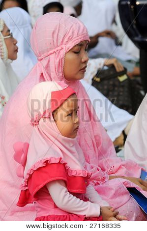 JAKARTA, INDONESIA - SEPTEMBER 20: Mother and daughter perform prayers outside a mosque on Hari Raya, the end of a month of fasting called Ramadan September 20, 2009 in Jakarta.