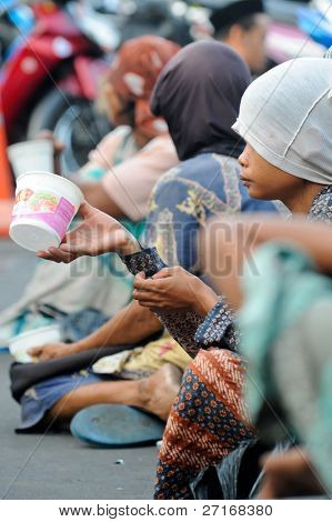 JAKARTA, INDONESIA - SEPTEMBER 20: Poor beggars line the path to the mosque in hope of receiving some charity on Hari Raya, the end of a month of fasting called Ramadan September 20, 2009 in Jakarta.