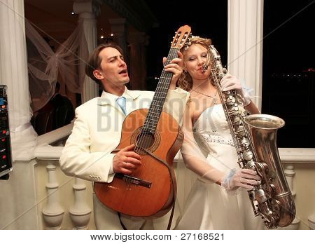 The bride and groom are entertained guests at a party in honor of their wedding