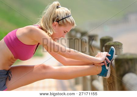 Young woman stretches along the pathway