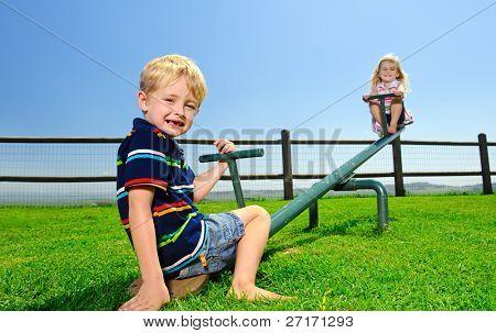 Niños jugando en el balancín en el patio de recreo