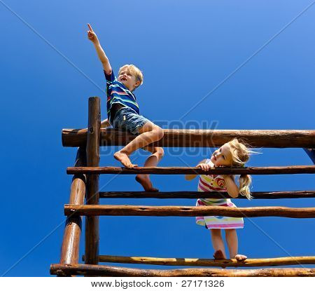 Two young children sitting at the top of playground equipment