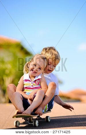 Two young children sitting and playing with skateboard