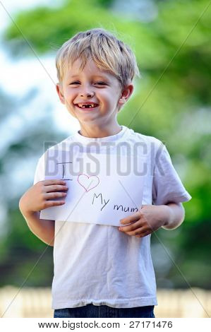 Young boy holds up a handwritten sign of 'I love my mum'