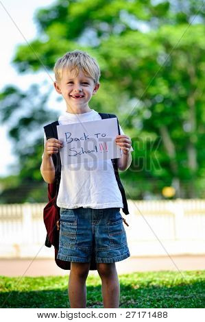 """Young boy holds up handwritten sign """"Back to school!"""""""