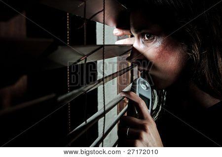 ängstlich misshandelte Frau spähen durch die Blinds zu sehen, ob ihr Mann ist Zuhause. Sie ist contemplatin