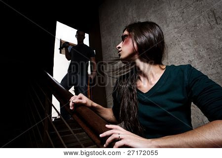 Concept of domestic abuse. Battered woman escaping from man silhouetted at the top of the stairs, in fear of more violence