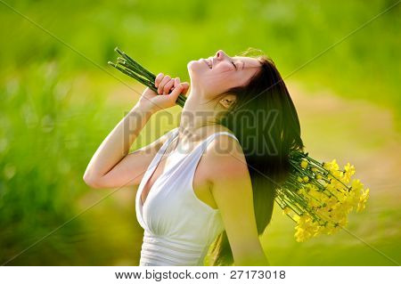 candid adorable girl in white dress is carefree with flowers in green field during spring.
