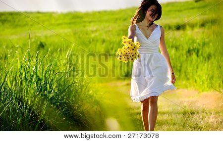 Sincera pulando despreocupada adorável mulher no campo com flores, pôr do sol de Verão.