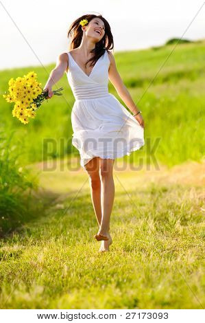 Candid skipping carefree adorable woman in field with flowers at summer sunset.