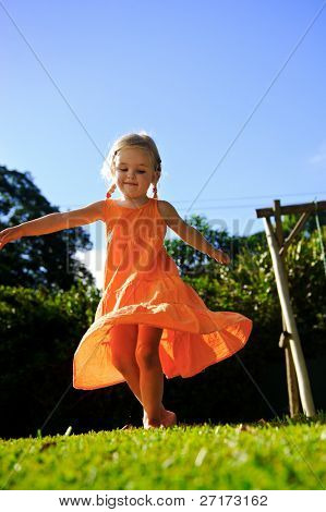 beautiful girl twirls in the sunset in her orange dress with blonde hair in pigtails