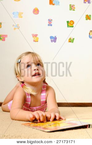 cute young blonde girl thinks about the book she is reading at preschool