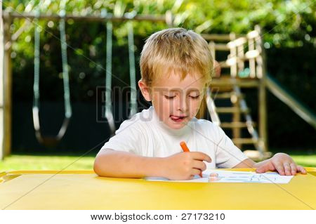 young boy thinks hard about what to draw with his crayons at kindergarten