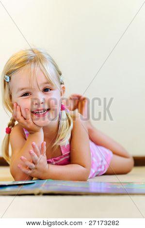 süße blondes Mädchen mit Zöpfen lacht und liest ein Buch im kindergarten