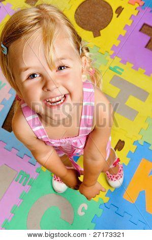 jovem loira sorri como ela aprende o alfabeto no infantil, primário