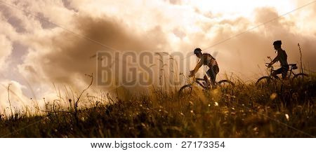 Happy couple riding bicycles outside, healthy lifestyle fun concept. silhouette at sunset panoramic