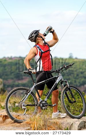 young man drinks water to quench thirst after a mountain bike cycle