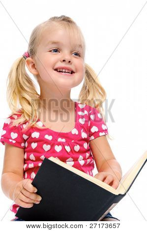 young blonde child is smiling while reading a book isolated on white