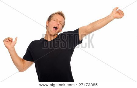 Casual young man is so sleepy he stifles a yawn in studio, isolated on white
