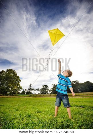 Junge fliegt seinem Kite auf einem geöffneten Gebiet. eine bildliche Analogie für die Bestrebungen und mit dem Ziel hoher