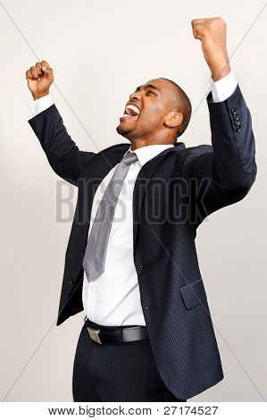 Attractive black professional raises his fists in joy and triumph