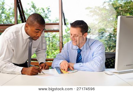 African businessman mentors his white associate on how to choose colors appropriately with color tags