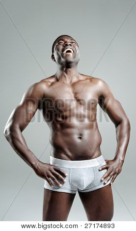 Confident masculine model laughing out loud in his underwear in studio