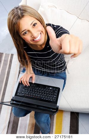 Pretty girl is smiling and giving the thumbs up with laptop
