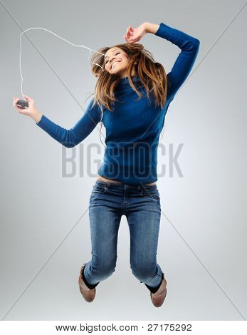 Young woman listening and dancing to music with earphones, having fun and relaxing