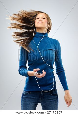 Young woman listening to music with earphones, having fun and relaxing