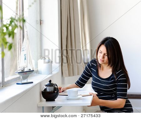 Beautiful brunette sitting by the window, reading and having some tea