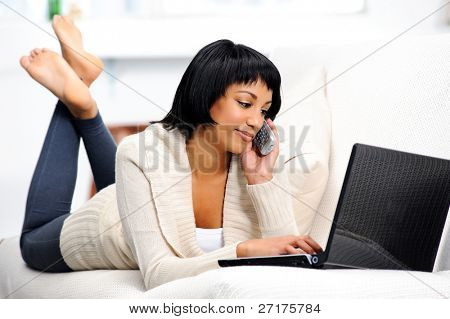 Pretty woman lying on the couch, using her laptop and talking on the telephone at the same time
