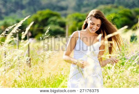 carefree woman laughs and skips through a meadow at sunset