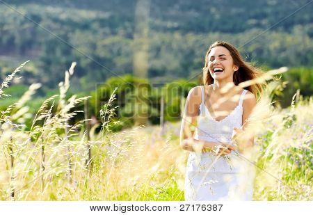 mulher despreocupada ri e ignora-se por meio de um prado ao pôr do sol