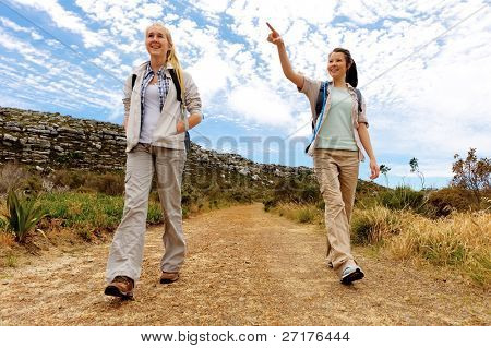friends walk a dirt road together outdoors, healthy hiking on a sunny day