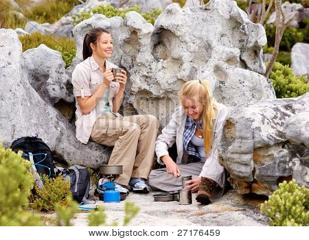 two girls hiking in the great outdoors have stopped to have some coffee and cook some canned food