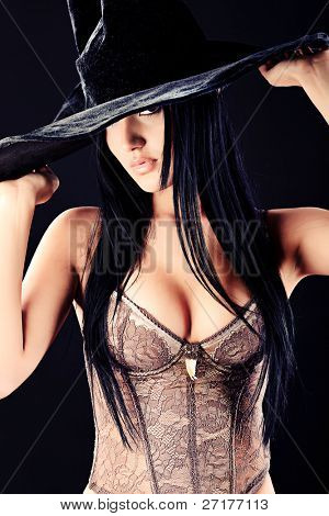 Charming halloween witch over black background.