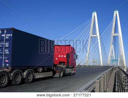 blue-red truck driving on cable-braced bridge