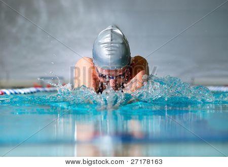 Frau schwimmt mit der Brust im Hallenbad
