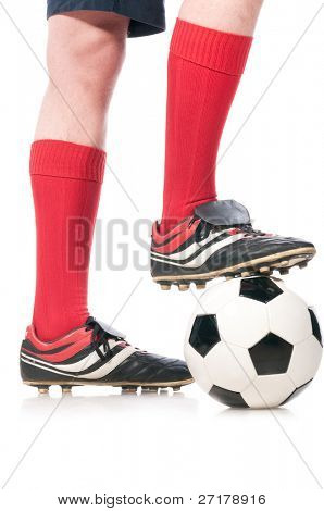 legs of soccer player with ball isolated on white